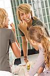 Teenage boy brushing his teeth with his sister looking at him