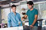 Verser le vin dans des verres pour son ami dans la cuisine de l'homme