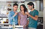 Three friends drinking wine in the kitchen
