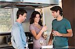 Trois amis, boire du vin dans la cuisine