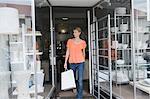 Femme sortant d'un magasin après le shopping