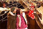 Junges Paar mit Weihnachtsstrumpf am Baum hängen