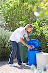 Frau Wasserflaschen in die Mülltonne werfen