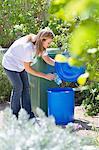 Frau Wasserflasche in die Mülltonne werfen