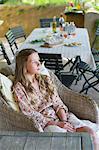 Petite fille à la recherche de suite avec de la nourriture sur la table en arrière-plan
