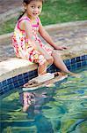 Fille assise au bord de la piscine avec le bateau de jouet dans l'eau