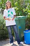 Porträt einer Frau halten Wasser Flaschen in der hand neben Recyclingbehälter