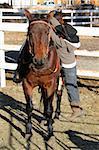 Young horse rider climbing off his horse