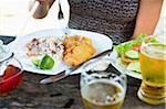 Frau Essen Mahlzeit von gebratener Fisch, Reis und Bohnen und Salat am Strand Café, nahe Paraty, Rio De Janeiro, Brasilien