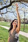 Femme touchant des fleurs sur les arbres dans le parc
