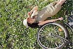 Femme couchée dans l'herbe avec vélo