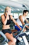 Femme sur téléphone portable sur l'appareil d'exercice