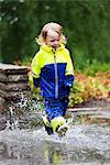 Boy walking in puddles in park