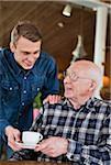 Grandchild serving coffee to grandfather