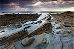 Rockpools and ledges beneath a cloudy sky, Sandymouth Beach, Cornwall, England, United Kingdom, Europe