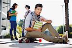 Student sitting on skateboard outdoors