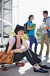 Smiling student sitting on skateboard