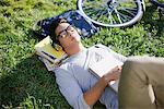 Student listening to headphones in grass