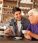 Men reading newspaper in cafe