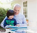 Older man and grandson reading together