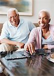 Vieux couple jouer aux dominos en riant