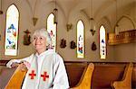 Reverend sitting in church pews