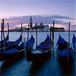Time lapse view of gondolas docked in urban pier