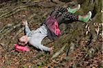 Adolescente se trouvant sur les racines des arbres
