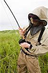 Fly fisherman portant des poissons de protection contre les moustiques pour le saumon sur la rivière Mulchatna dans la région de la baie de Bristol, sud-ouest de l'Alaska, l'été