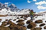 Backpacker femme traversant les buttes de neige et de la toundra au-dessus de la rivière Babel, contrefort sud sur le flanc ouest des monts de la révélation, l'été dans le centre-sud de l'Alaska