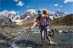 Backpacker femme traversant la rivière de Babel sous les contreforts du Sud sur le flanc ouest des monts de la révélation, l'été dans le centre-sud de l'Alaska