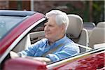 A senior man driving a convertible sports car