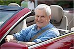 A cheerful senior man driving a convertible sports car