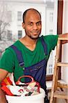 Un homme tenant un seau de peinture fournit la préparation d'une échelle