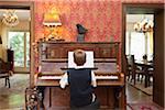 Ein Junge auf einem altmodischen Klavier üben