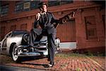 Gangster tenant la mitraillette se penchant sur les voitures anciennes