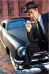 Homme en costume avec des cure-dents en se penchant sur les ailes de voitures anciennes