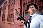 Gangster avec Tommy gun sur le regard dehors à l'extérieur du bâtiment
