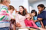 Teacher reading book to multi-racial group of young preschool children