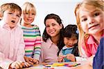 Happy young children with kindergarten teacher