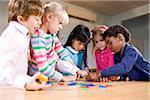 Preschool children working together on puzzle