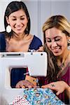 Young women stitching fabric on sewing machine