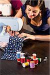 Young woman stitching fabric on sewing machine