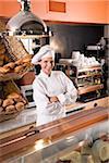 Baker working behind bakery shop counter