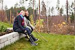 Couple sitting in back yard garden with gardening equipments