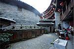 Femme cuisine au cour du Zhencheng Lou au village de Hongkeng, Yongding, Fujian, Chine