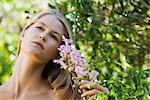 Jeune femme tenant la branche de fleurs, levant, portrait