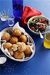 Dish of risotto balls with salad