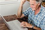 Older man using laptop in kitchen