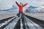 Frau springen auf den Weg in die verschneite Landschaft
